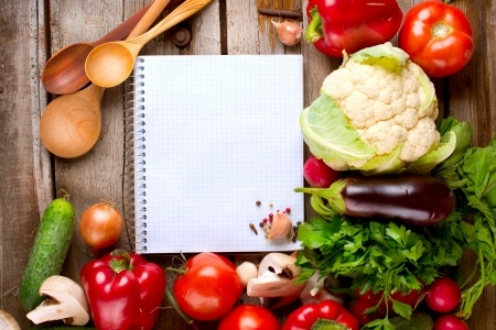15622406 - open notebook and fresh vegetables background  diet