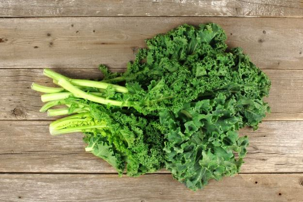 38189776 - bunch of fresh kale over a wooden background. overhead view.